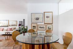 Mesa de vidro com base de madeira, parede galeria e cadeiras Series 7 na sala de jantar desse apê.
