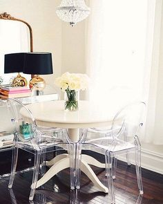 Clear ghost chairs, a crystal chandelier and gilded French mirror add major glam appeal to this petite dining corner.