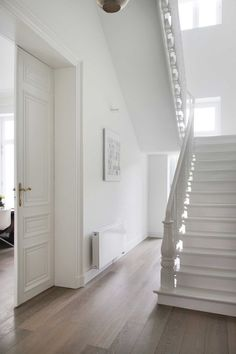 This all-white staircase makes a minimalist's dream of an entryway. White Hallway, White Staircase, White Walls, Building Stairs, Staircase Remodel, Interior Minimalista, Wooden Stairs, Level Homes, Stairways