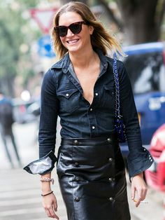 A dark denim shirt is paired with a leather pencil skirt, chain shoulder bag, and Céline sunglasses