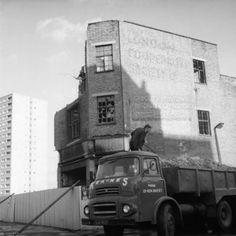 negative - A man stands with a loaded lorry besides a partially demolished building in Kilburn 1972