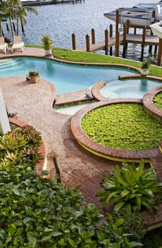 This lakeside yard boasts an irregularly curved pool with embedded jacuzzi, wrapped in traditional red brick patio and standing next to a boat dock. Backyard Pool Designs, Small Backyard Patio, Swimming Pool Designs, Pool Landscaping, Outdoor Pool, Desert Backyard, Backyard Ideas, Blue Haven Pools, Simple Pool