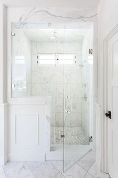 A seamless glass and white wainscoting enclosure accents a walk-in shower fitted . A seamless glass and white wainscoting enclosure accents a walk-in shower fitted with carrera marble hex floor tiles surrounded with square marble wall tiles. Bathroom Renos, Bathroom Flooring, Bathroom Renovations, Small Bathroom, Marble Bathrooms, Dyi Bathroom, Bathroom Showers, Master Bathroom, Marble Showers