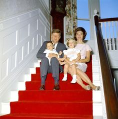 President John F. Kennedy and First Lady Jacqueline Kennedy sit with their children, John F. Kennedy, Jr. and Caroline Kennedy, on the stairs inside the Auchincloss home at Hammersmith Farm, Newport, Rhode Island.