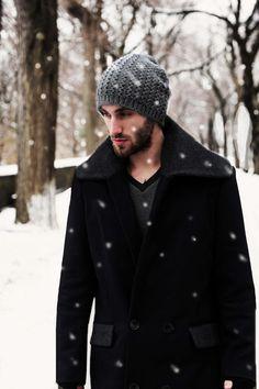 мужчина в черном пальто и серой шапке