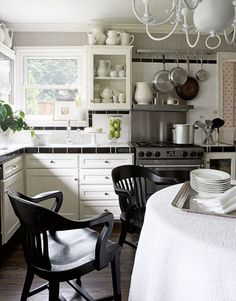 The owners avoided an extensive kitchen remodel by painting existing cabinets Benjamin Moore Brilliant White and installing inexpensive black and white tile on counters and backsplashes. An extensive ironstone collection overflows from shelves to walls. Vintage jurors' chairs were picked up at assorted flea markets and antiques shops and stained ebony. The table is covered in cotton matelassé from Peacock Alley. The range is Jenn-Air.
