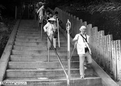 Shikoku pilgrimage summer 2013. Henro, as the pilgrims are called in Japanese, walking down the steps from a temple. They are wearing traditional white clothes - hakui is the jacket and oizuru is the vest. On their heads some are wearing the wooden hat called sugegasa. And of course as every pilgrim should, they are carrying the staff, kongozue.
