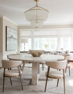 Contemporary open plan dining room features an Aerin Jacqueline Two-Tier Chandelier hung above a round gray oak dining table surrounded by modern cream leather dining chairs placed on a gray rug.