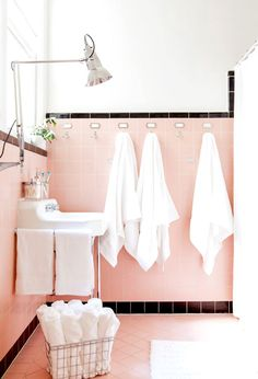 Hanging towels beside sink in light pink bathroom