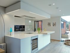 bulthaup b3 kitchen in Alpine White laminate and structured oak veneer bar top. Corian worktops from Counter Production. Miele and Westin appliances.