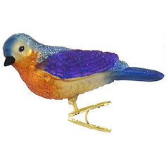 "This charming Western bluebird is ready to migrate into the branches of your tree this Christmas!  With vivid glazes and sparkling glitter accents, our exquisitely detailed songbird is 2"" tall 4¼"" wide and crafted of glass.  This breathtaking Western bluebird clip-on ornament is a must-have for that special bird watcher in your life!Symbol of the Blue Bird card included"