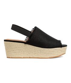 Black. Platform sandals with an elasticized strap around heel, wedge heels, and braided jute trim around sole. Faux leather lining and insoles. Rubber soles