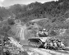 """""""Hongchon, 15 May 1951, Marines take cover while an M26 Pershing tank engages atarget further down the valley."""""""