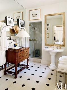 A vintage French bistro mirror hangs above the antique pedestal sink in the poolhouse bath | archdigest.com