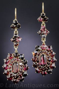 A glistening double-tiered frame of faceted almondine garnets with bright burgundy flashes surround an elongated oval center stone, surmounted by trefoil and quatrefoil clusters in these ravishing 1 7/8 inch long drop earrings from early-twentieth century eastern Europe. Crafted in gilded metal with 14K wires.