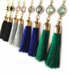 "Silk tassel dangle earrings with colored framed gemstone on gold ear wires. Available Colors: Black Silver Royal Blue Green Tassels are approx. 2"" long."