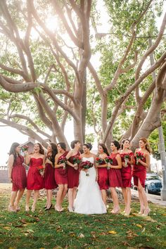 Bridesmaids in red dresses with mismatched textures, with red bouquets