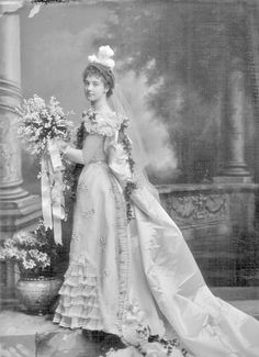 "Margery Waterlow, daughter of George Sidney Waterlow and his wife, Charlotte Elizabeth Beauchamp.   copyright V&A. ""...charmingly attired in white. The skirt and bodice were trimmed with frills of pleated chiffon edged with satin, and the train was of white satin, with a cluster of lilies of the valley and trails of ivy on it. A trail of ivy, catching in clusters of lilies was placed right across the bodice..."""