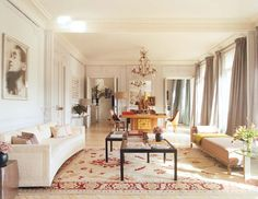 His living room combines mid-century furniture, antiques, and family heirlooms to create the perfect Parisian pad. #livingroom #midcentury #furniture #white #sofa