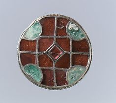 Disk Brooch, Frankish, 6th century. Silver, garnets, gilt with patterned foil backings, emeralds.