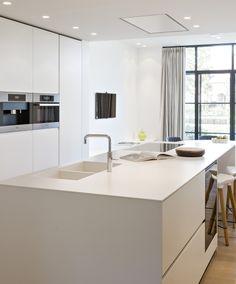 Vloerverwarming: waar wel en waar niet? Foto: www.dekton.com (keukeneiland • wit • inbouwspoelbak • ingebouwde oven • verhoogd keukeneiland • wit werkblad • parket)