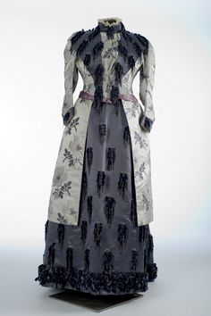 Emile Pingat (1820–1901), Paris, Afternoon Dress, 1880–1888. Silk, silk damask, silk satin, lace, beads, glass, metal, chenille. Gift of the von Stade family. Collection of Shelburne Museum. 1982-4.238     This two-piece silver and navy blue afternoon dress was originally owned by Dolly Fischer von Stade (1859–1888), who would have worn it to an elegant dinner party. Physical evidence indicates that during the construction the bodice was altered professionally to accommodate an expectant…