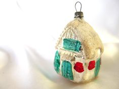 This vintage Christmas ornament was made in a blow mold. The silver and aqua house / cottage ornament has a white mica roof and bottom, warm red