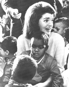 Four-year-old Bobby Johnson is held by Mrs. Kennedy during a Christmas party for the young and elderly at a Bronx community center in New York, 1965.
