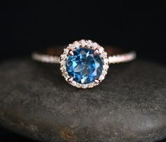 This Beautiful 14k Gold Single Halo Ring Features a flawless Natural London Blue Topaz Round measuring 7mm and surrounded with Natural Diamonds.