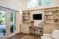 The Front Area Interior With Built In Tv Cabinet Design Along With The Home Office Under The Arched Windows With Simply Wooden Chair And Cozy Armchair Towards The Front Door A Small Guest House with French Doors and Patio Area Home design