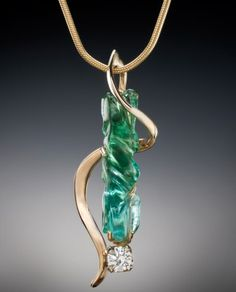 A tendril of 14kt gold entwines a green tourmaline and a diamond in a striking pendant by Nancy Ellinghaus. American Made.