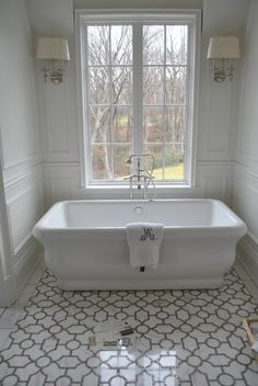 Tile, freestanding tub and sconces.