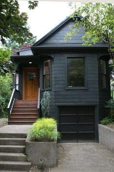 Angela had the exterior of her 1906 house painted black. She likes that it gives the antique home a modern edge. #houseexteriorcolors