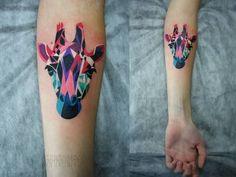 Imagino que no peito do pé essa tattoo ficaria perfeita. Girafa feita com formas geométricas e muito colorida.