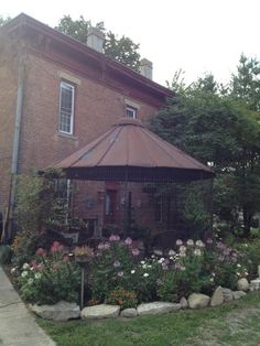 "from Myra Glandon! Myra commented: ""This is our gazebo made out of an old metal corn crib. We positioned it outside the kitchen door of our old brick house. We enjoy sitting out here in the evenings, listening to the sounds and enjoying the breeze. It's very nice to sit out here when it rains, and listen to the rain on the metal roof. It has a salvaged stone floor, and a vintage rustic chandelier. It's earthy and simple and reminds me of my life growing up on a farm."
