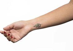 Tiny botanical wrist tattoo by Georgia Grey
