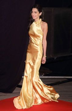 """George and Amal Clooney, at the Tokyo premiere """"Tomorrowland"""",May 25,2015. Amal Clooney looks stunning and elegant in a beautiful marigold bias cut satin Maison Margiela dress with a high neck accented by a delicate floral piece.This dress was especially created for her by John Galliano . This snap of her walking captures how stunning the dress was on the move.  Styled by Alexis Roche"""