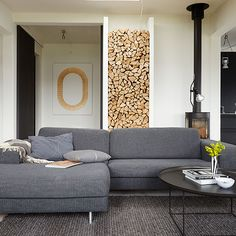 Open-plan living room with grey sofa, black coffee table and wood pile