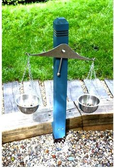 Outdoor scales made from a timber post, attached to a steel bar using chain to support the stainless steel bowls.