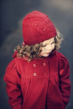 Girl's cherry red knit hat with butterfly pattern and beading, cherry red double breasted coat with pleats under yoke and at sleeve cap, such beautiful cascading curls  Doreen Kilfeather on flickr.