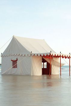 my creative mind whispered the following to me: 1. purchase a large tent -- 2. remove existing fabric and recover with drop cloths, using velcro so it can be easily disassembled -- 3. add a canopy, wood dowels and wood balls as finials