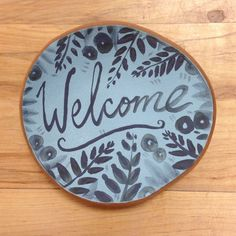 Welcome Sign in light blue with slate blue writing. Handmade ceramic wall hanging. Contact us with inquiries. Thank you.