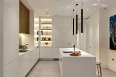 Kitchen Design Idea - White, Modern and Minimalist Cabinets   Warm wood above the stove, and soft lighting creates a cozier feel in this kitchen with all white cabinetry.
