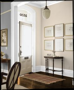 Have the wall to the left of the front door be one color giving the idea of an entry way; paint the rest of the living room walls a different color.