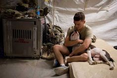 """Howard, the Tactical Explosive Detection Dog & his handler, Alexander, get ready for bed in Afghanistan. Image via Dog Bless You's Facebook page. (""""Dog Bless You"""" Philanthropist Donates 170 Dogs to Veterans   Dogster)"""