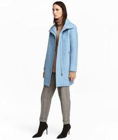 Lys blå. En rett skåret kåpe i filtet ullblanding. Kåpen har høy ståkrage med skjulte trykknapper, samt glidelås og vindlås foran. Sidelommer med glidelås.