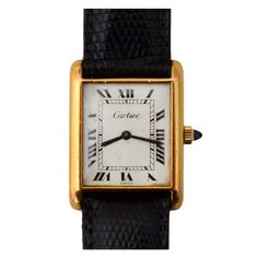 """CARTIER Tank Watch This is a medium size, Cartier gold vermeil tank watch with sapphire stem. It dates to the 1970's; runs well and requires winding. It comes with a brand new Cartier black lizard strap. The face measures 7/8"""" wide and 1 1/8"""" tall."""