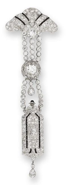 An art deco onyx and diamond lapel watch, circa 1925. Set throughout with calibré-cut onyx and old brilliant-cut diamonds, with millegrain detail, the triangular surmount suspending articulated rows of old brilliant-cut diamonds, terminating in a rectangular fob watch, the dial with Arabic numerals and an engraved bezel, diamonds approximately 6.60 carats total.