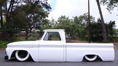 1964 1965 1966 Chev Chevy Chevrolet pickup truck slammed to the ground in the weeds laid out over wide white wall tires and sporting a shaved skin with a satin white paint job. Chevy C10, 1966 Chevy Truck, Classic Chevy Trucks, Chevy Pickups, Classic Cars, Bagged Trucks, Lowered Trucks, C10 Trucks, Pickup Trucks