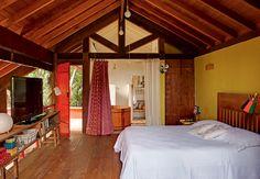 Ainda no projeto de Kita Flórido, o quarto é simples, mas passa a sensação de conforto. Uma colcha, presa com mosquetões, separa o banheiro. O assoalho rústico é de madeira de demolição